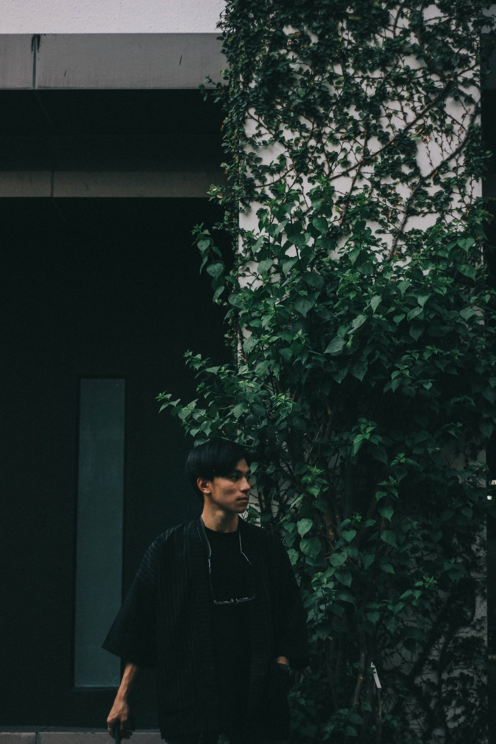 man standing beside wall covered with plants