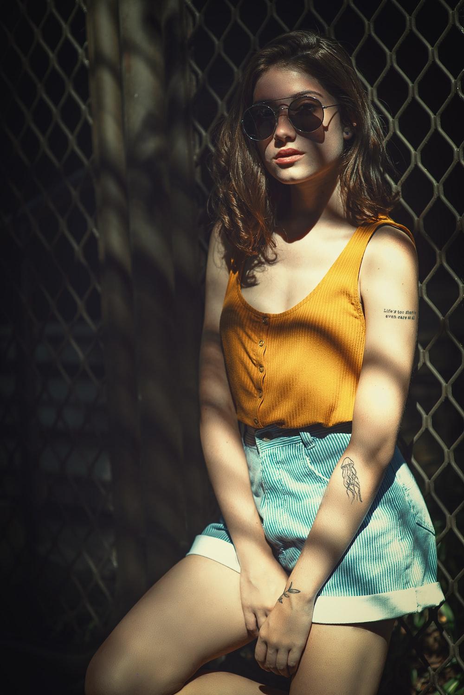 woman wearing yellow tank top lying on cyclone fence