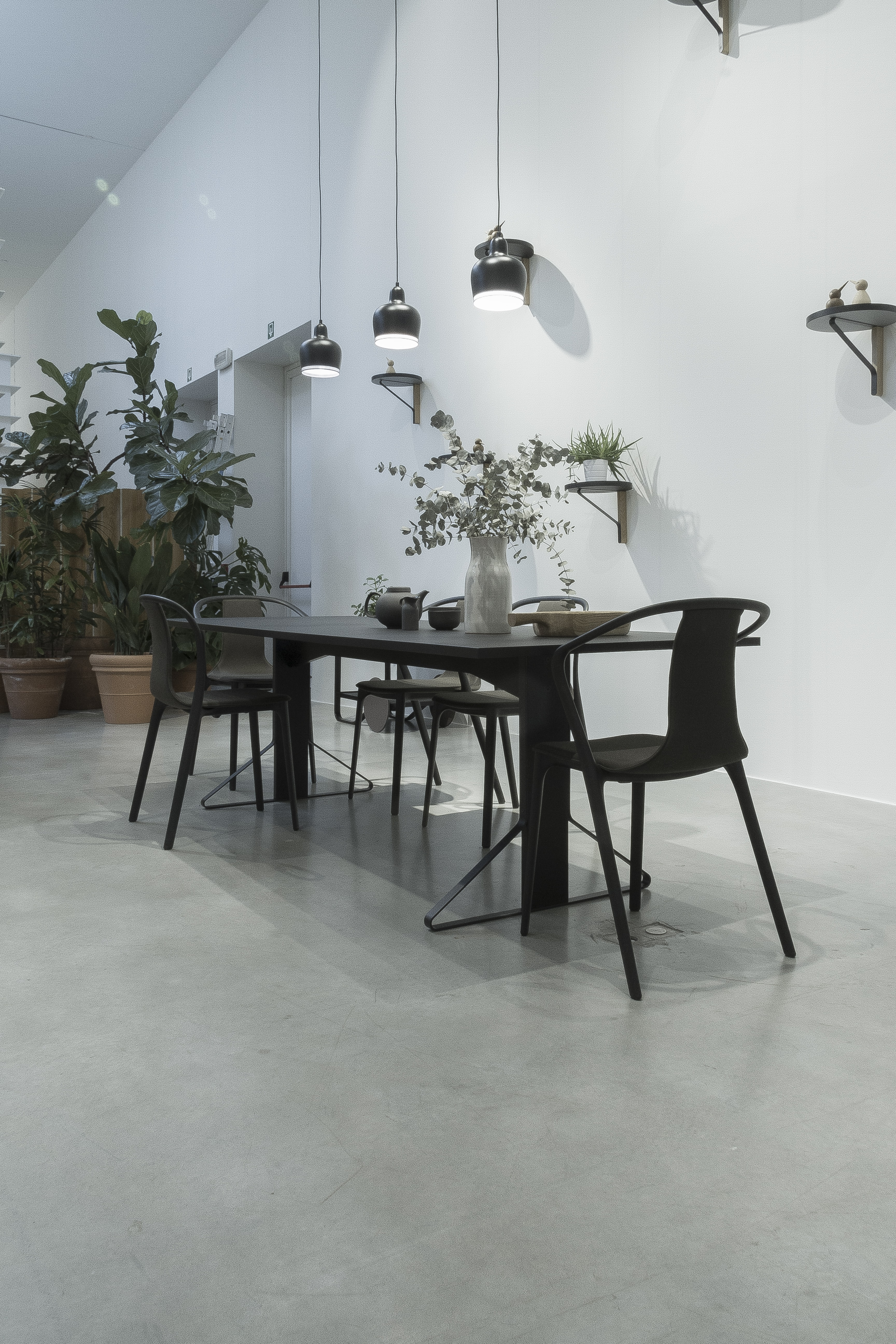 Black Wooden Table And Metal Chairs Near White Wall With Three Pendant Lamps Above Table Photo Free Chair Image On Unsplash
