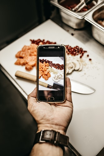 person holding smartphone while taking photo of cooked food