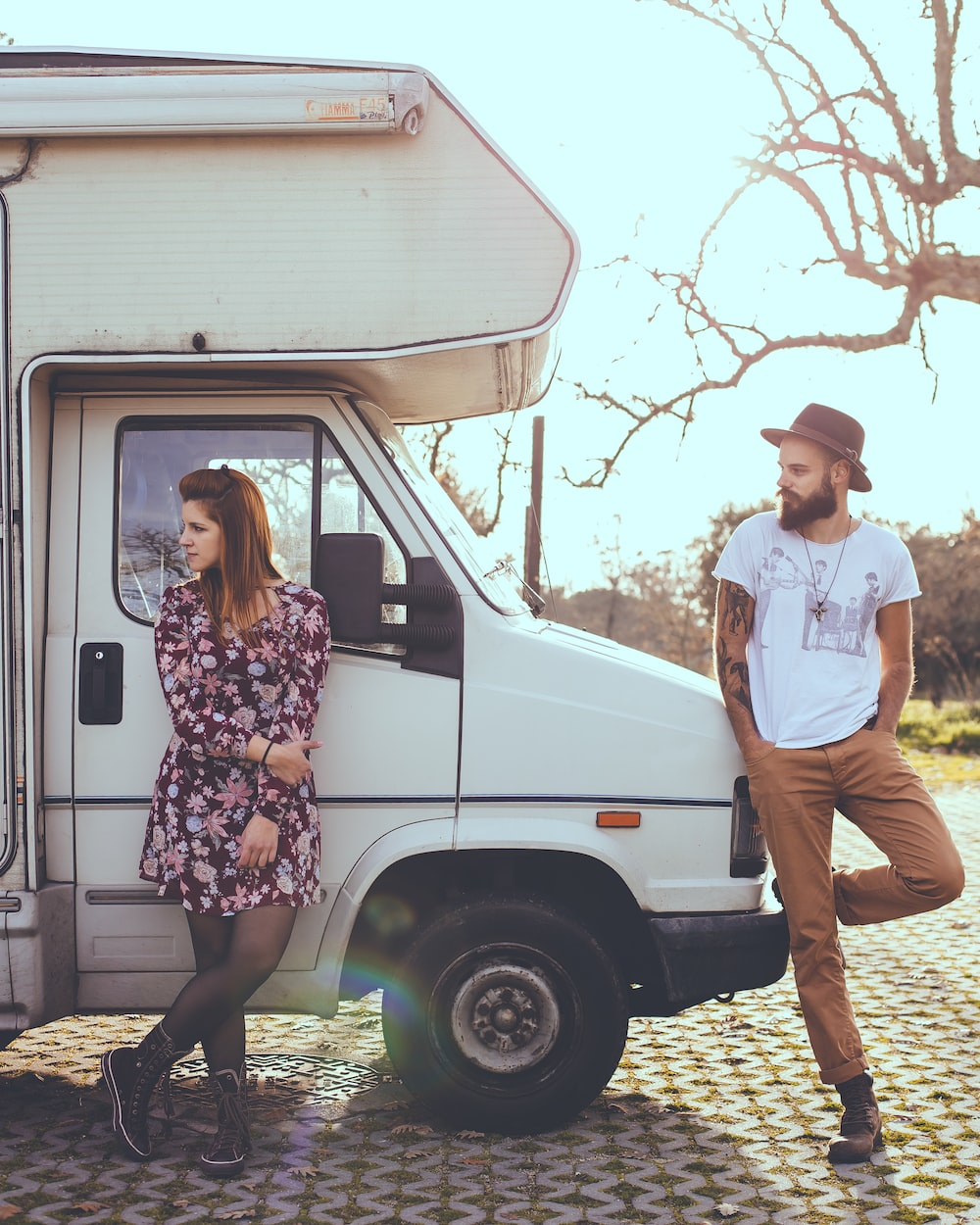 man and woman leaning on white RV trailer