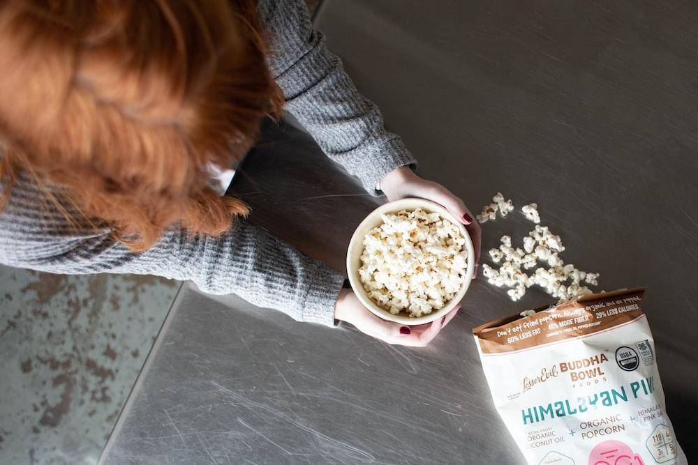 woman holding bowl of popcorn