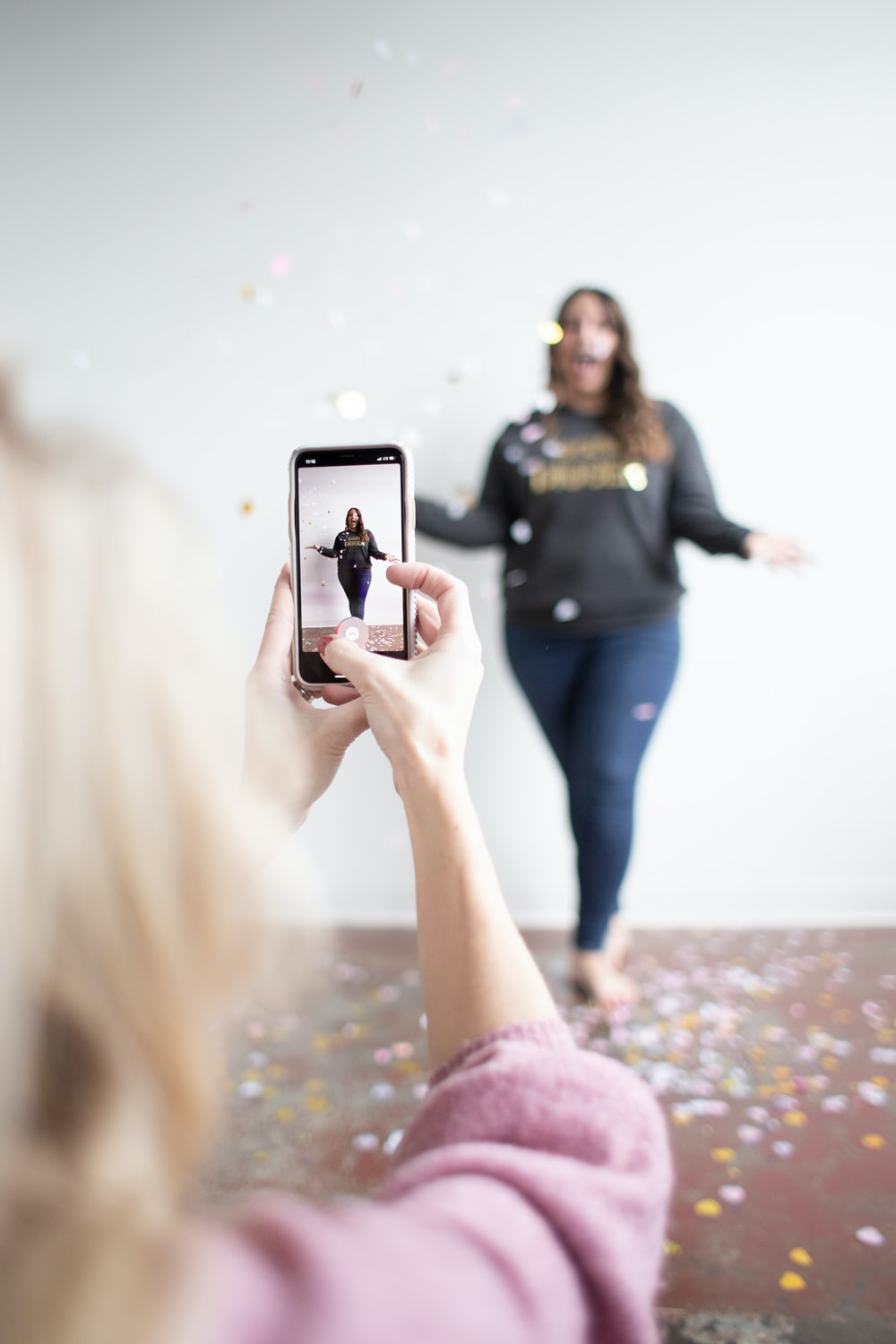 person holding white smartphone taking photo of woman wearing blue jeans
