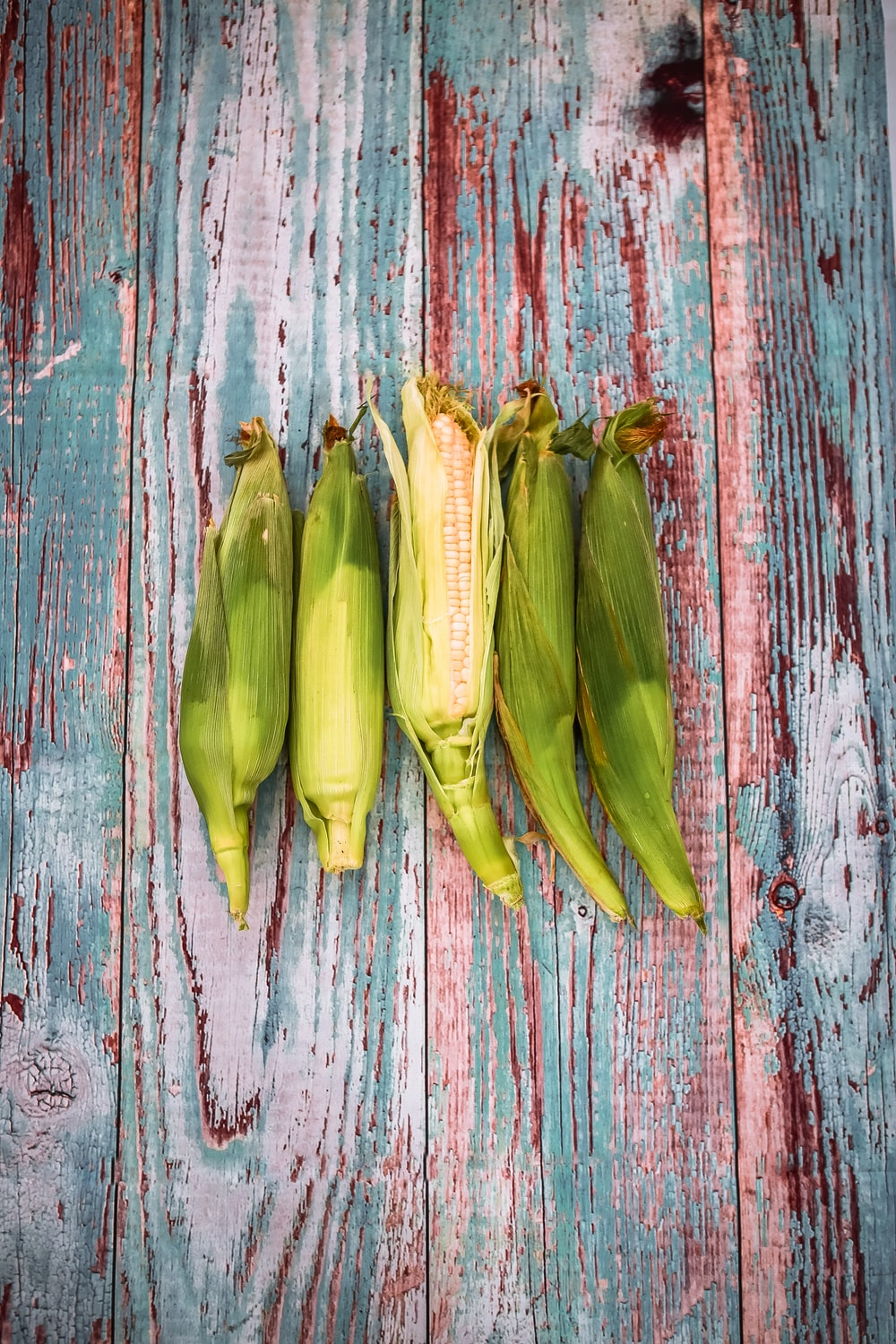 green corns on wooden surface