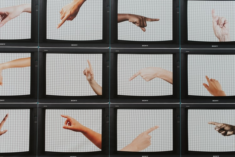 A photo of a grid of television screens, each with one hand pointing in a different direction.