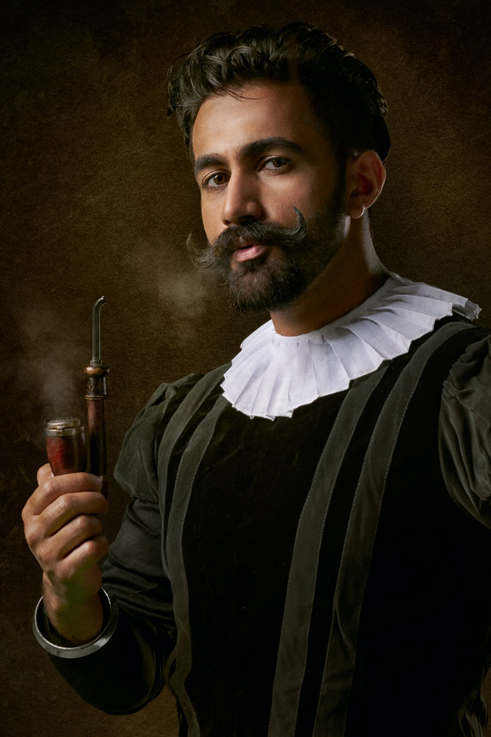 man wearing traditional clothes and holding smoking pipe