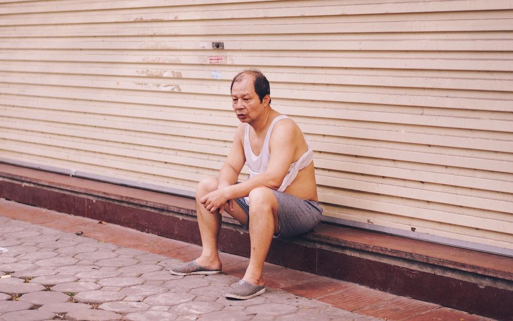 man sitting beside white shutter door