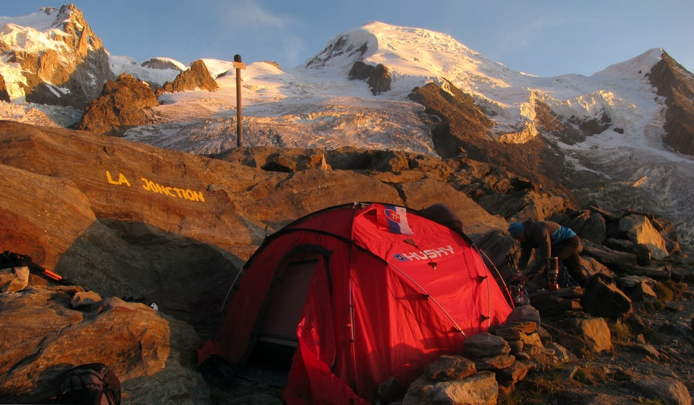 red and black dome tent on mountain peak