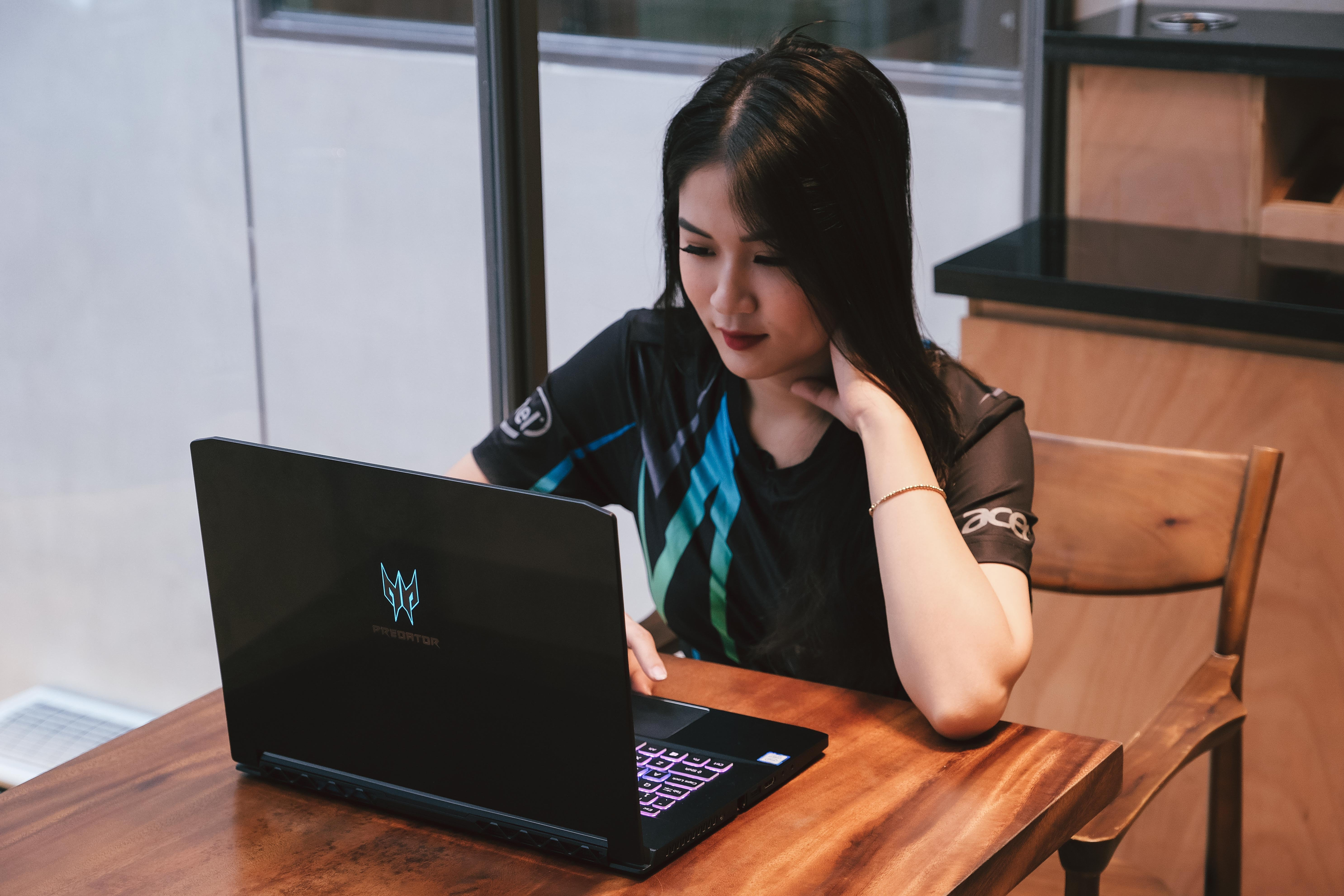 woman using laptop computer while sitting at the table