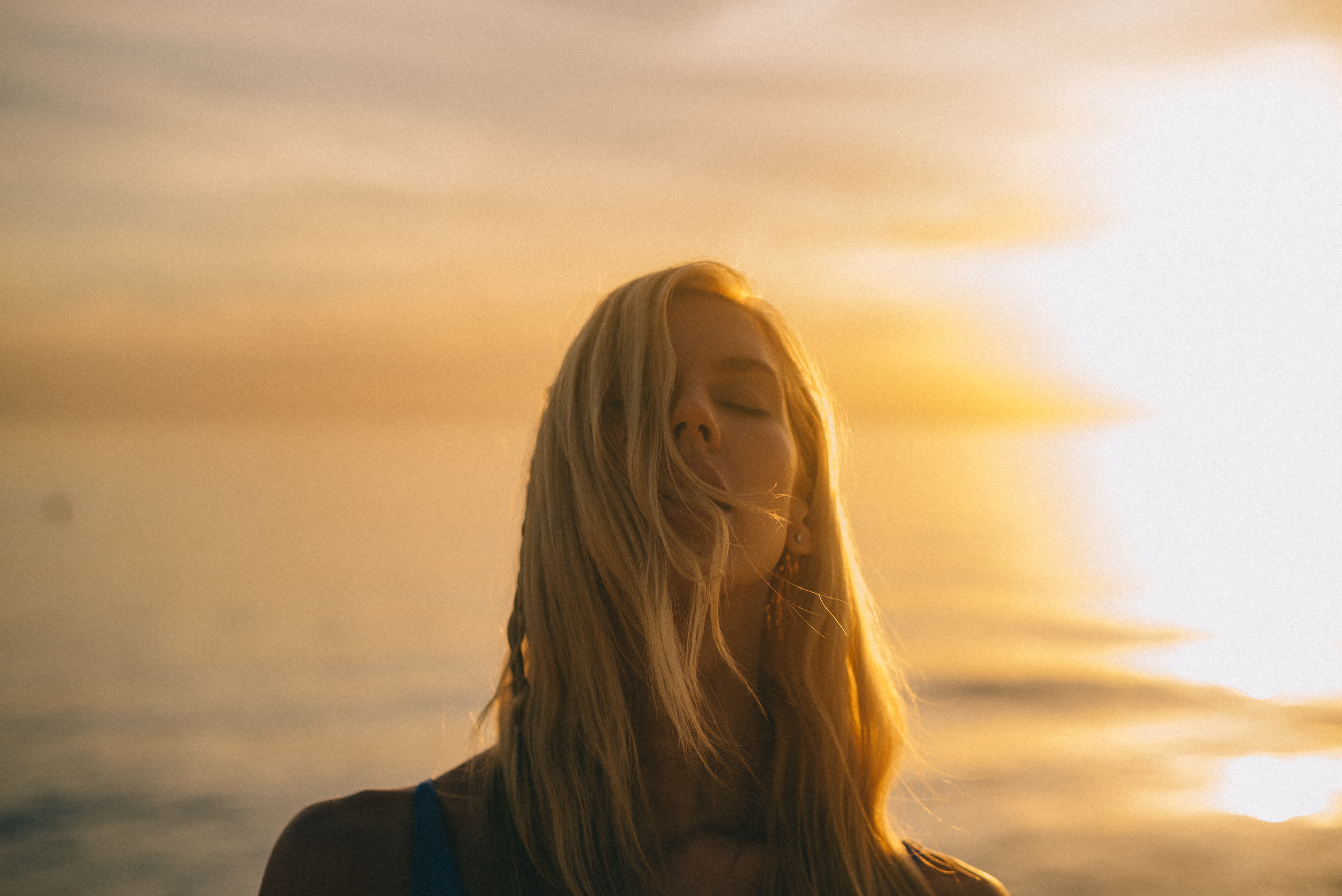 woman closing her eyes during golden hour