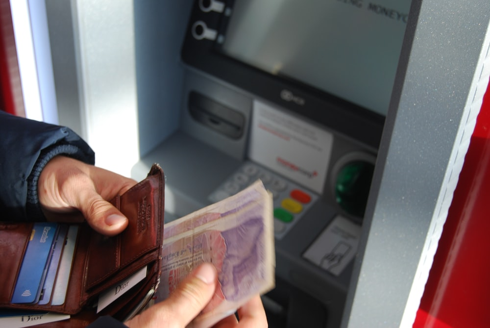 person holding brown leather wallet and banknotes