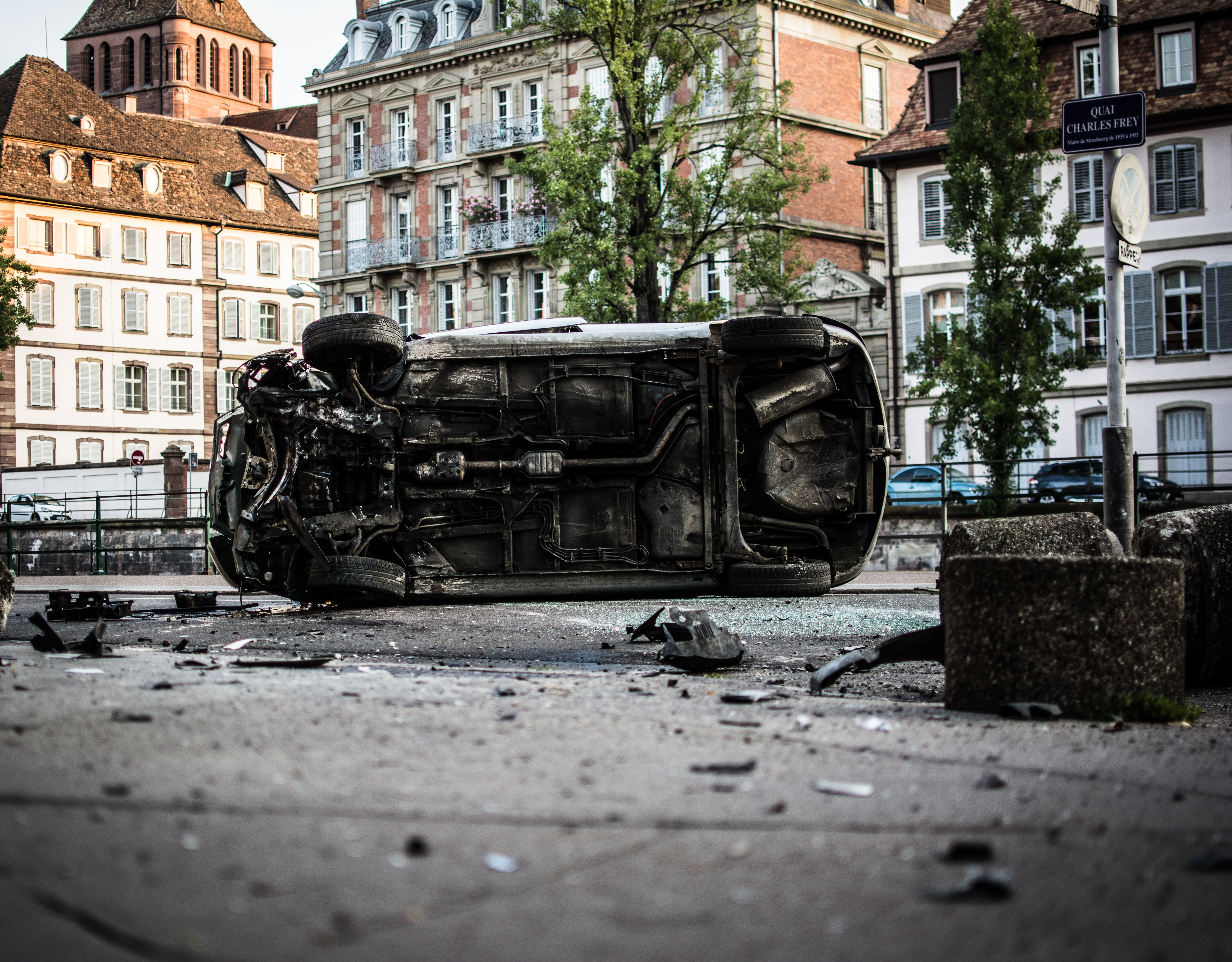 wrecked white vehicle near buildings during daytime