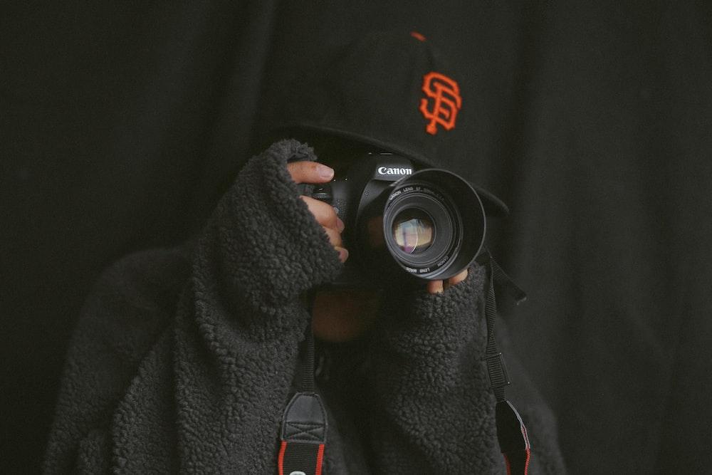 person using black Canon camera