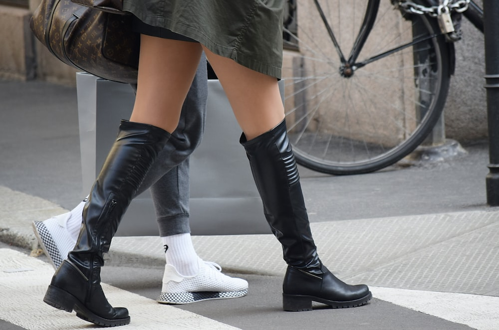 person wearing black leather boots