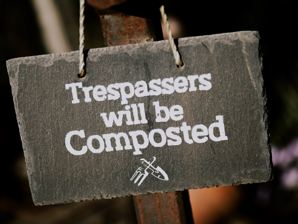 gray and white trespassers will be composted sign