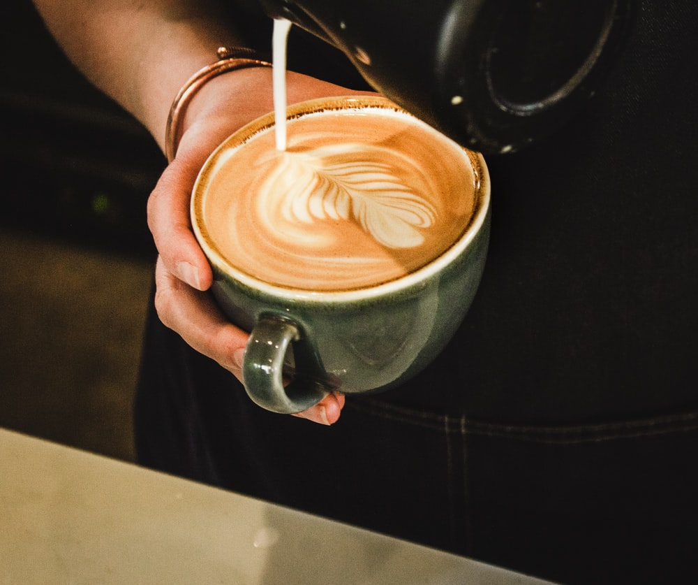 person pouring coffee on cup