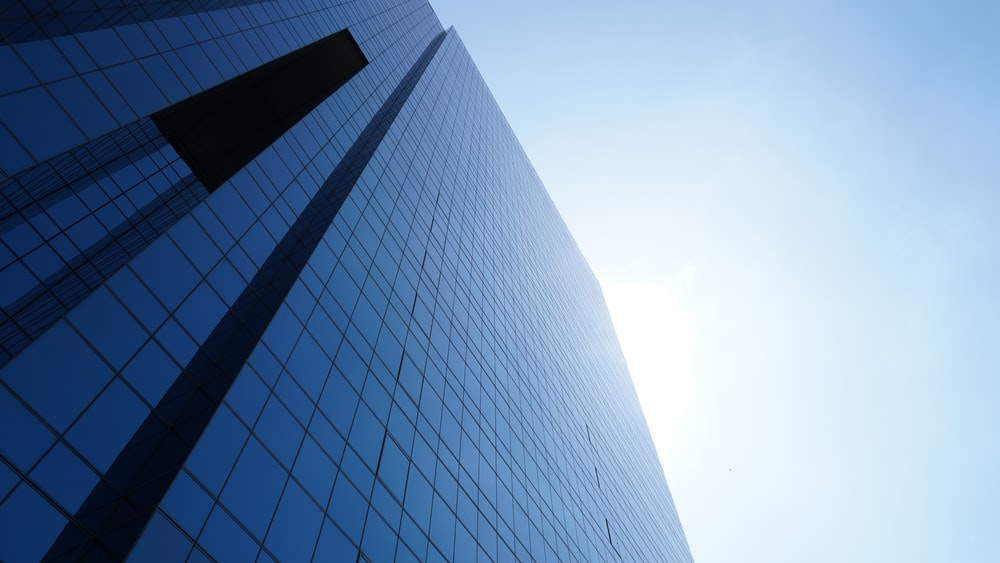 tall blue glass paneled building under clear blue sky