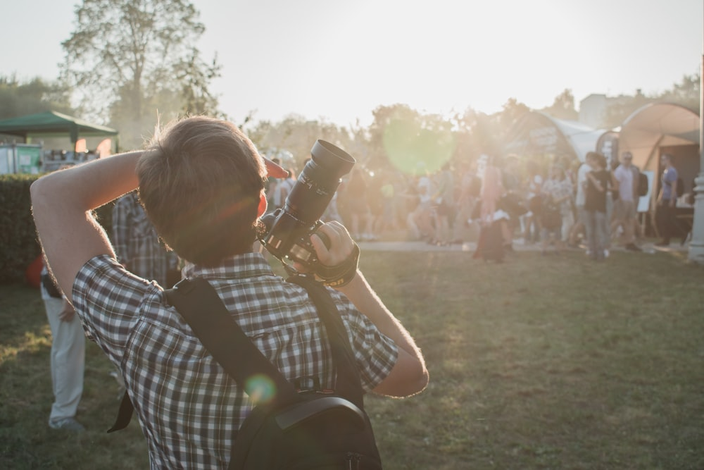 man in grey and white plaid shirt with backpack and DSLR camera on hand
