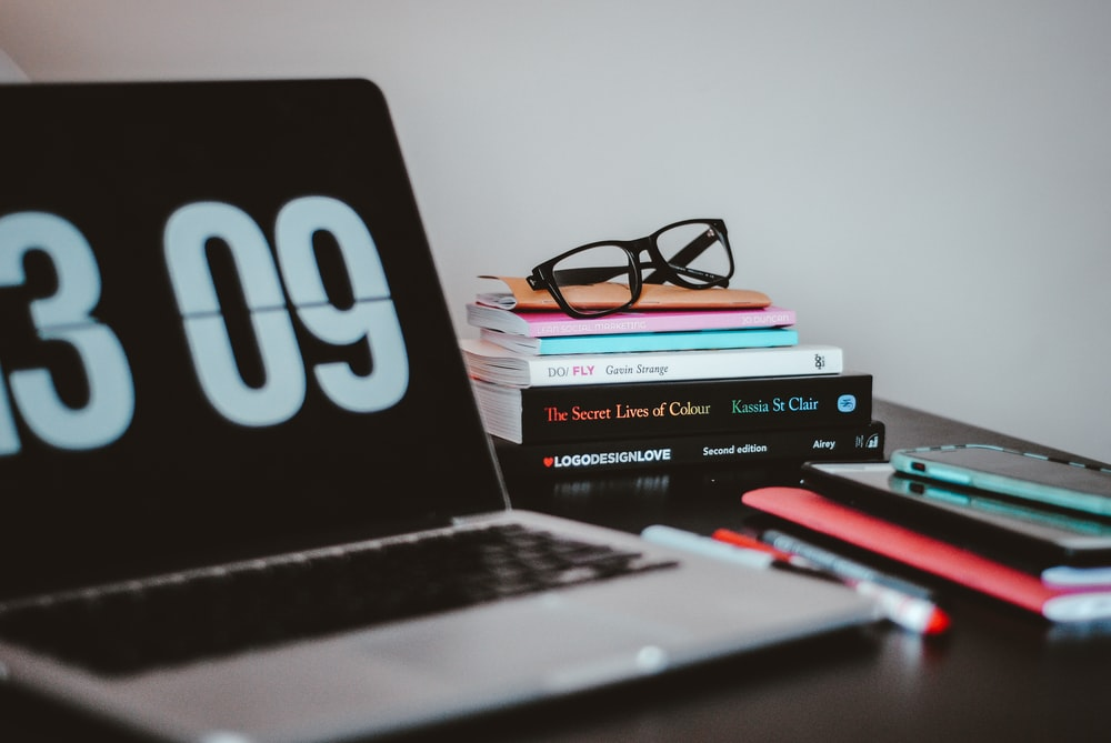 silver MacBook Pro near books