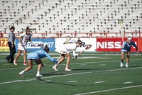 group of women playing lacrosse on field