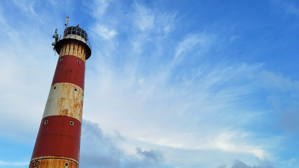 red and white lighthouse under clear blue sky