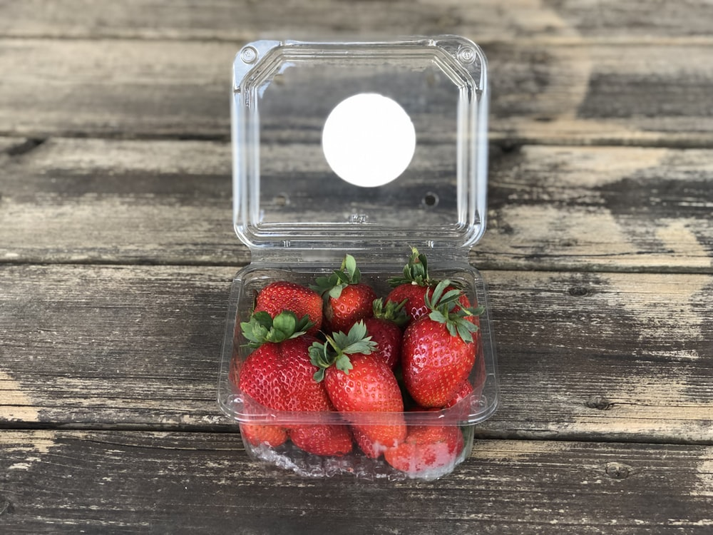pack of strawberries on brown wooden surface