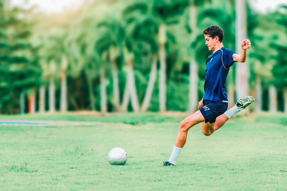 man trying to kick soccer ball