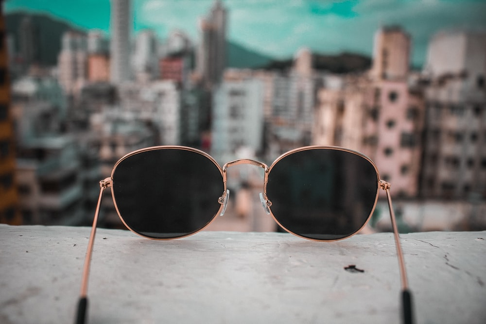 gold-colored framed sunglasses on white surface