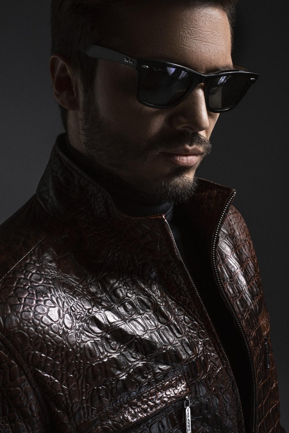 man wearing black leather jacket and sunglasses