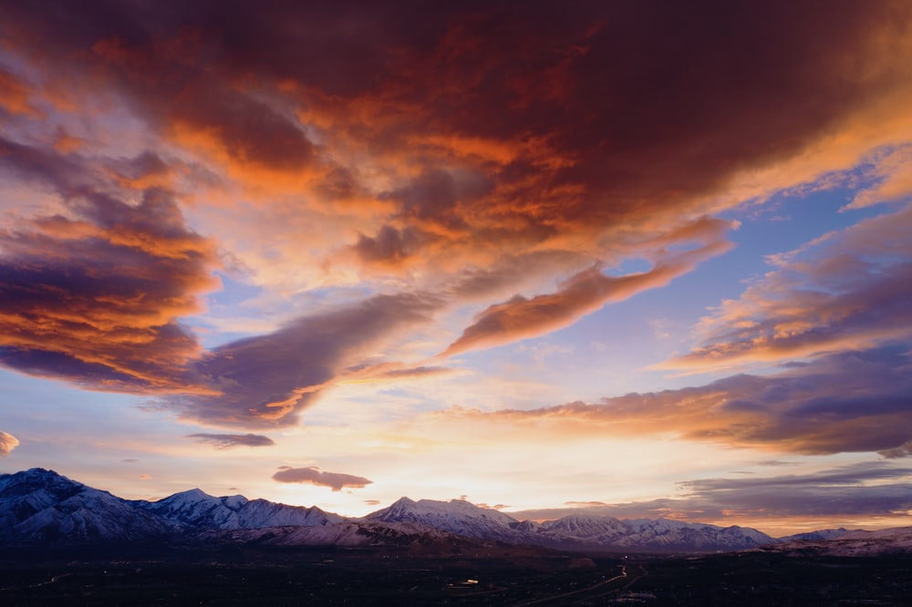 rocky mountain under cloudy sky during golden hour
