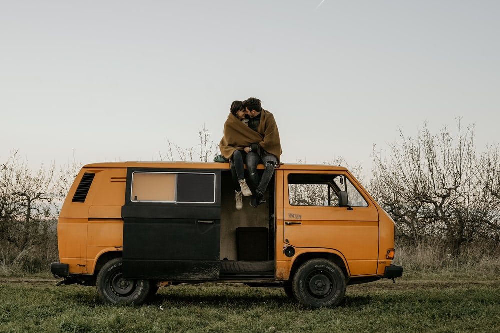 man and woman on yellow utility van