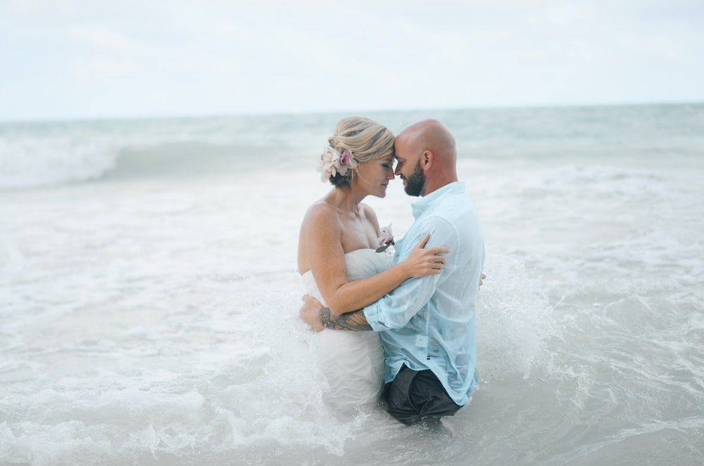 man and woman standing and almost kissing on body of water