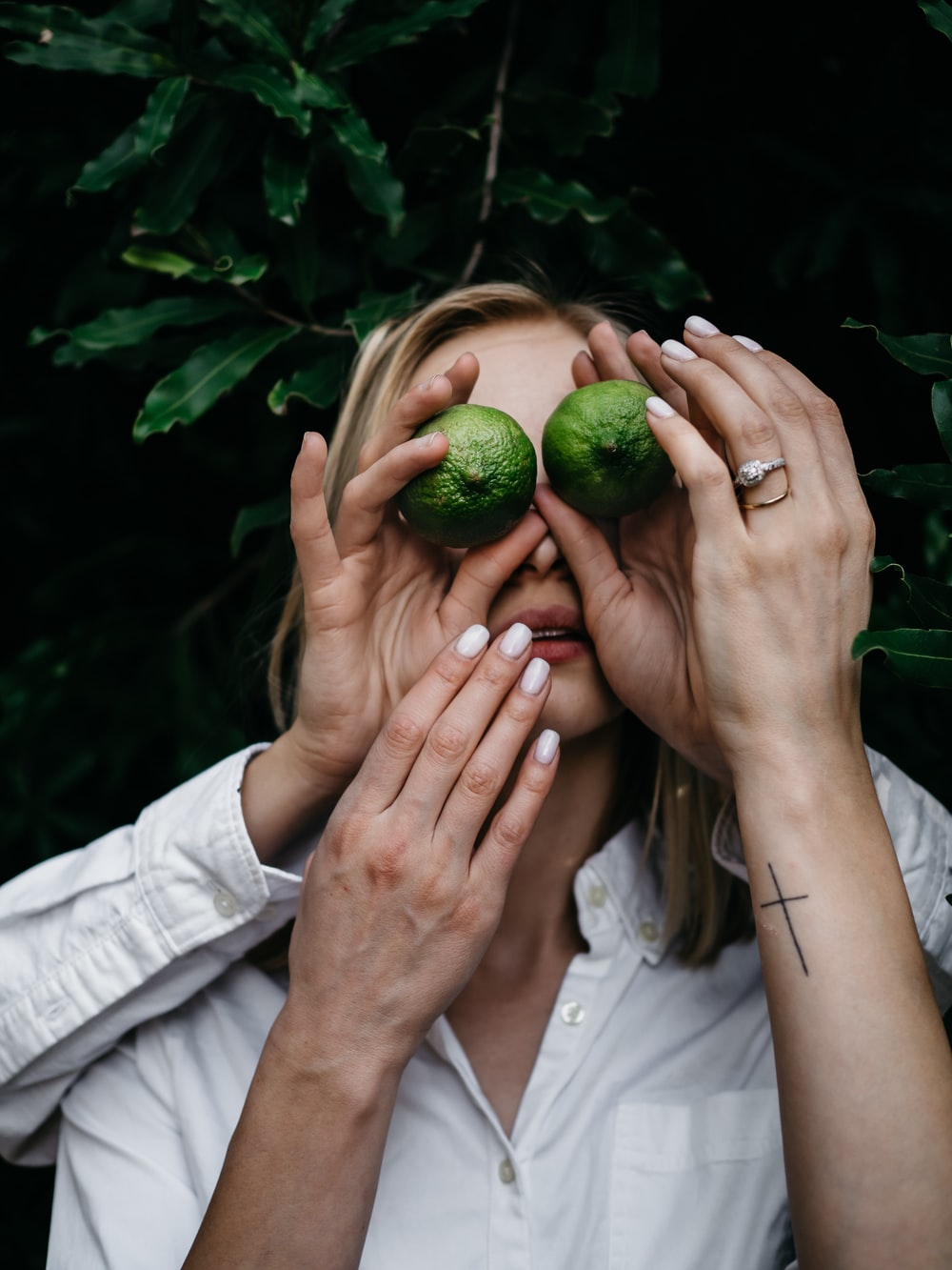 woman covering her eyes using green fruits