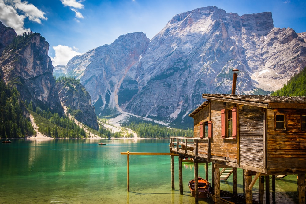 brown wooden house beside body of water overlooking rocky mountain during daytime