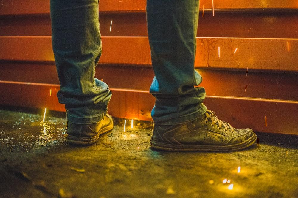 man wearing brown high-top sneakers