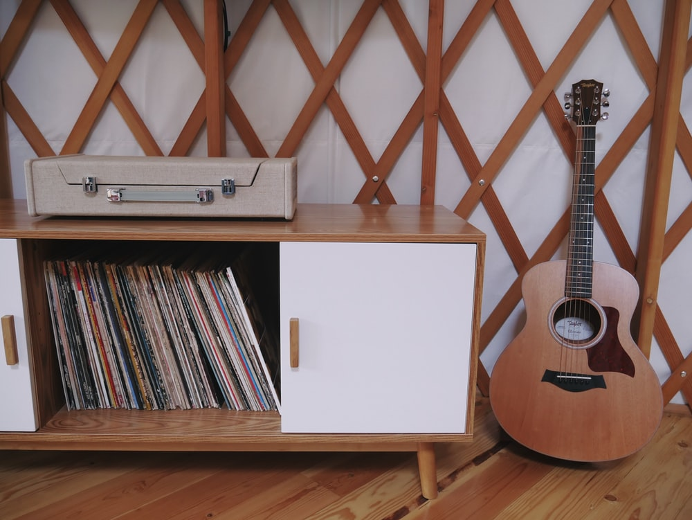 white sideboard beside guitar
