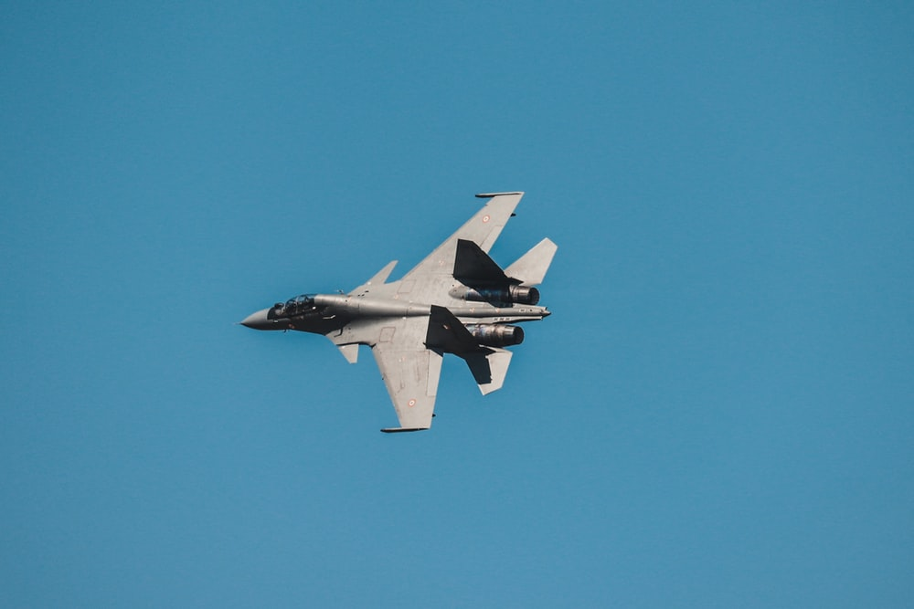 grey fighter jet under blue sky