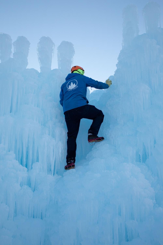 man climbing on ice during daytime