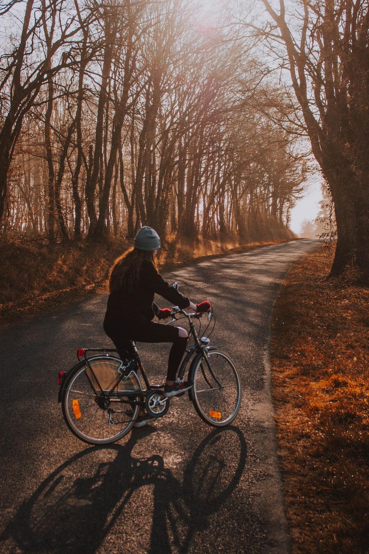 woman biking on gray concrete pavement