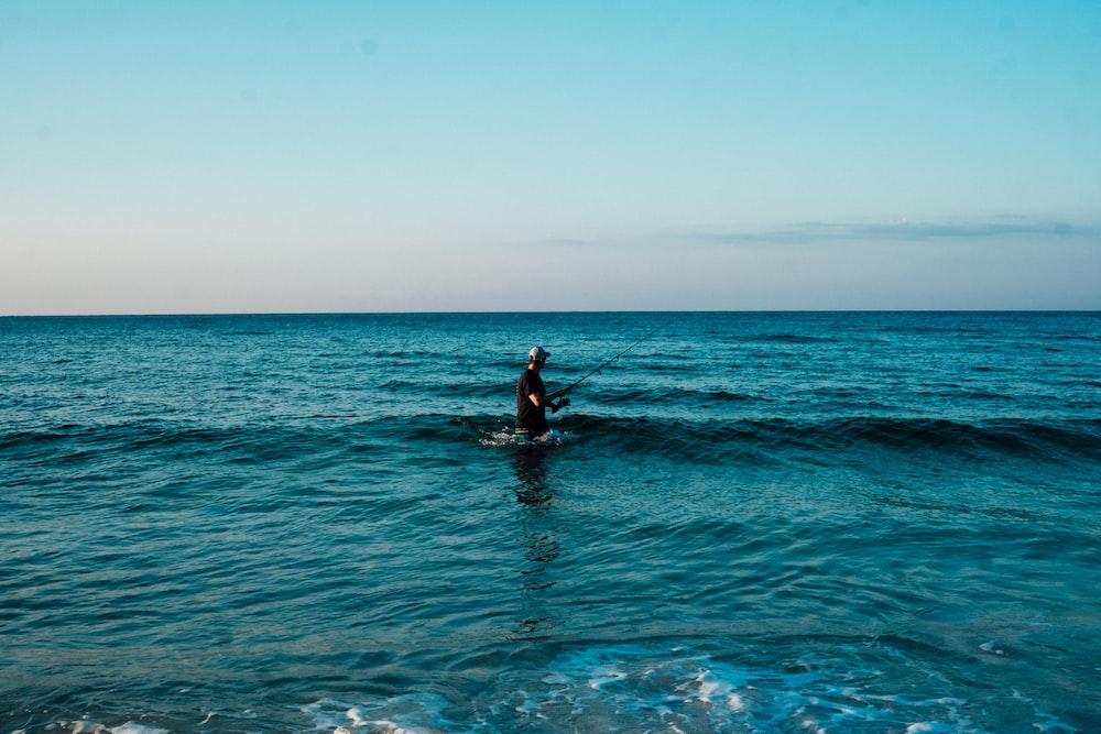 man fishing on body of water