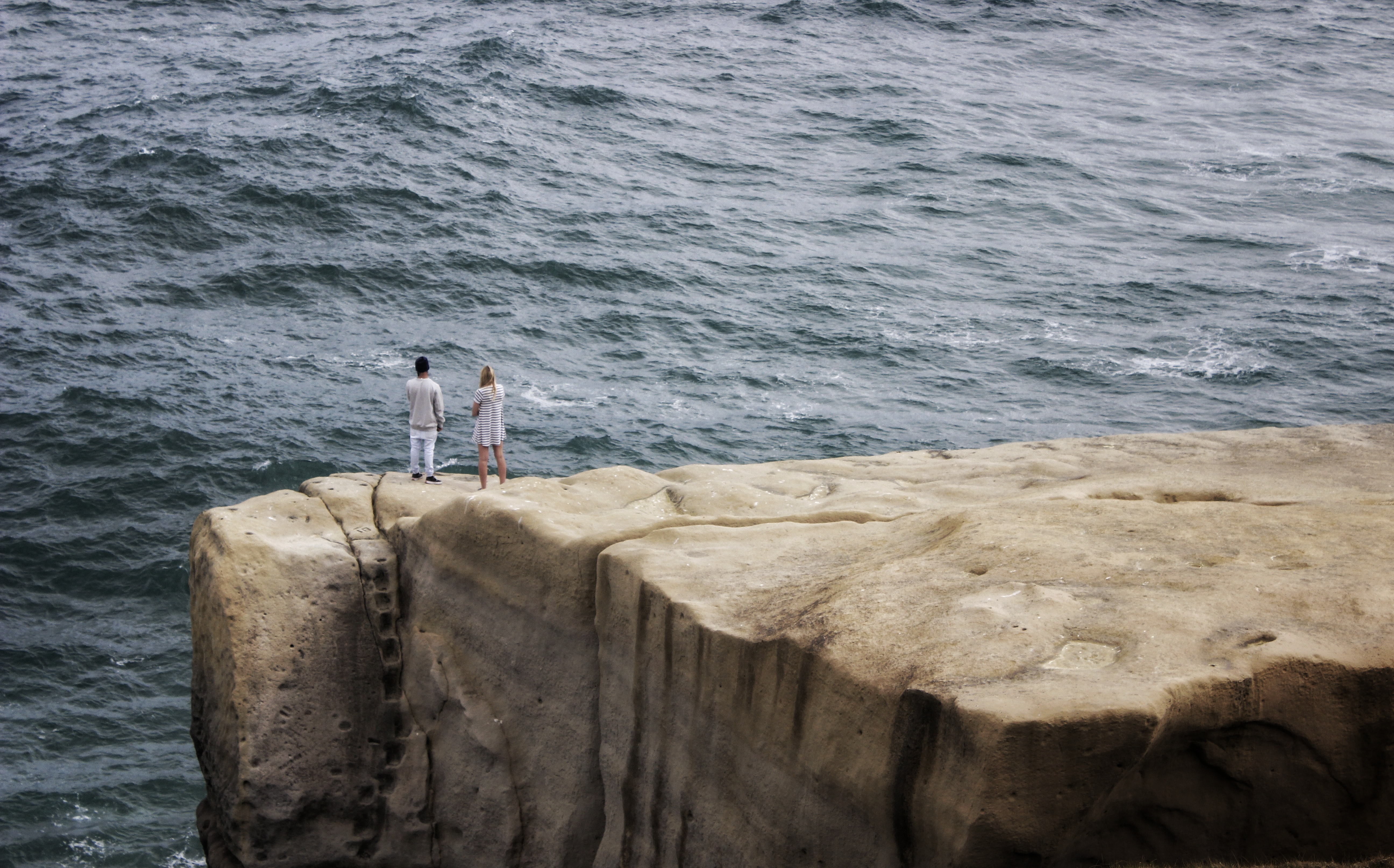 man and woman standing on cliff fronting sea