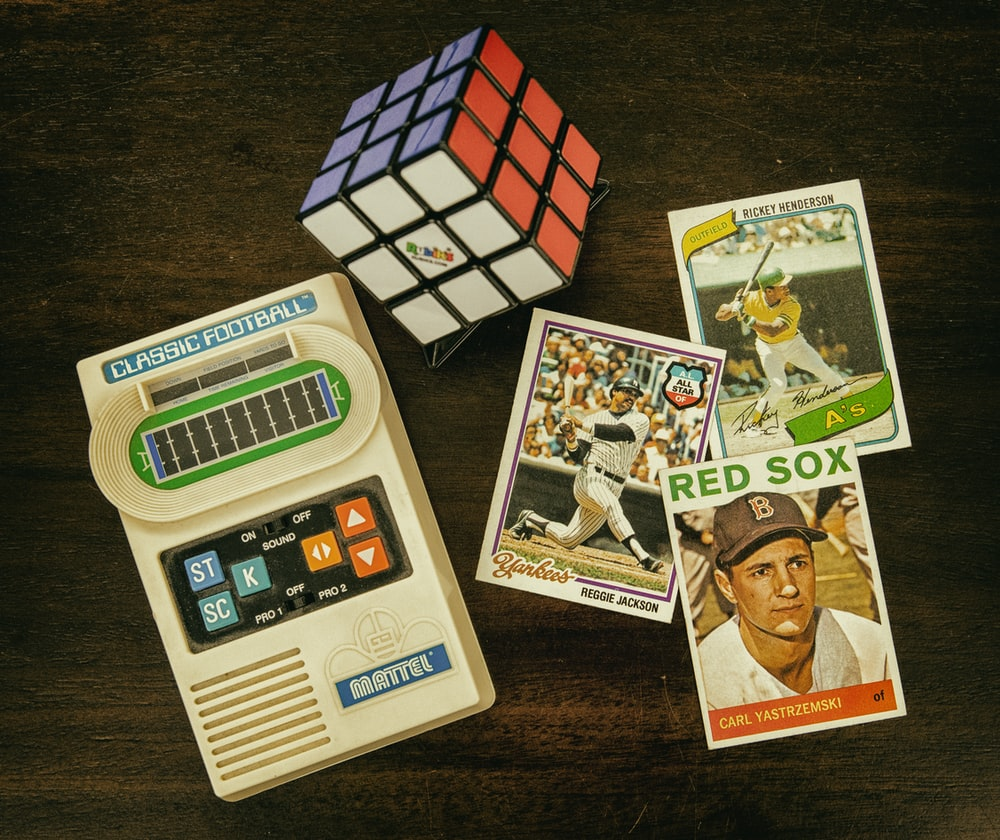 three baseball trading cards beside Rubik's cube and Classic Football handheld game console