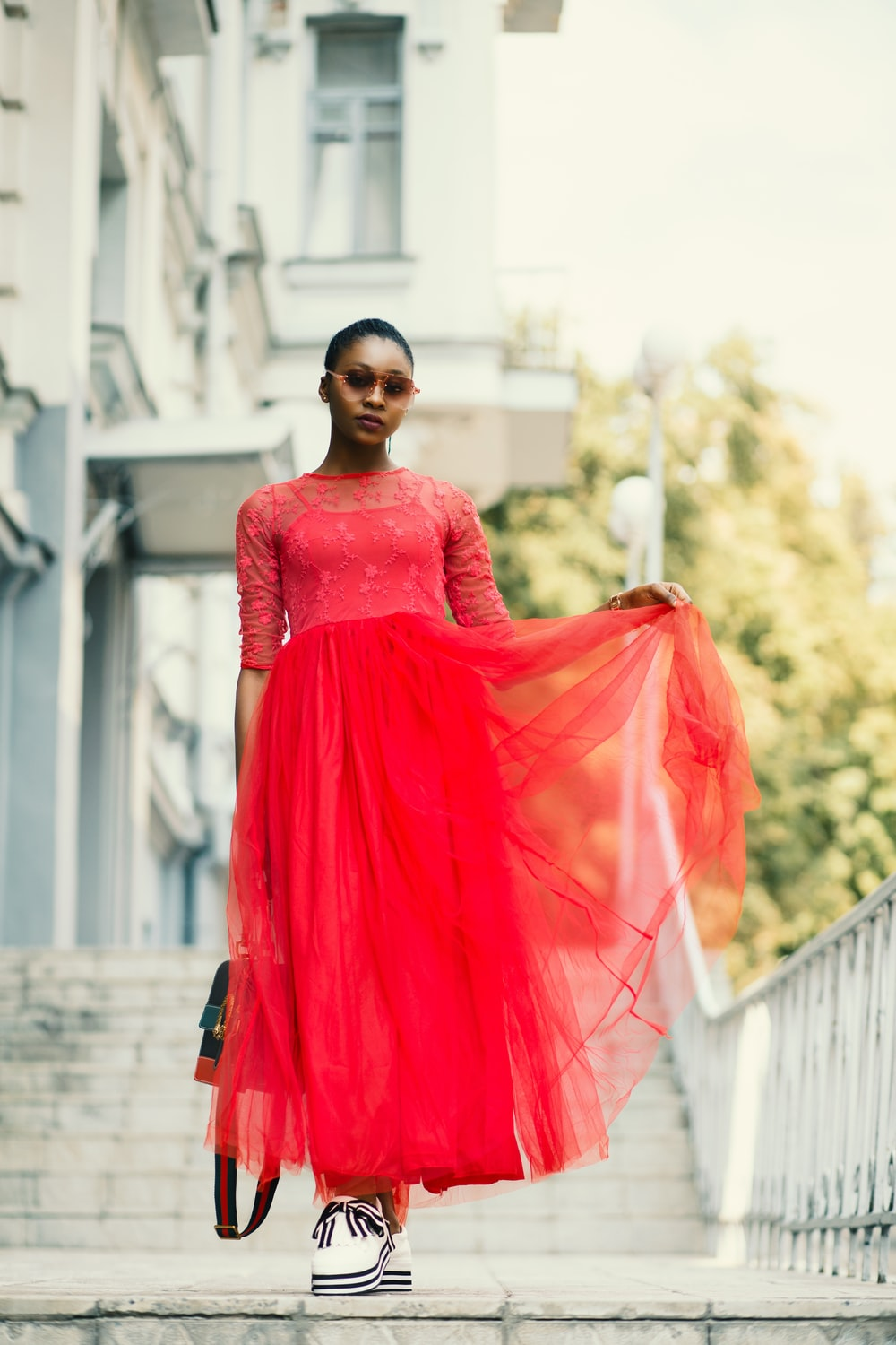 woman in red elbow-sleeved dress standing beside white metal rail