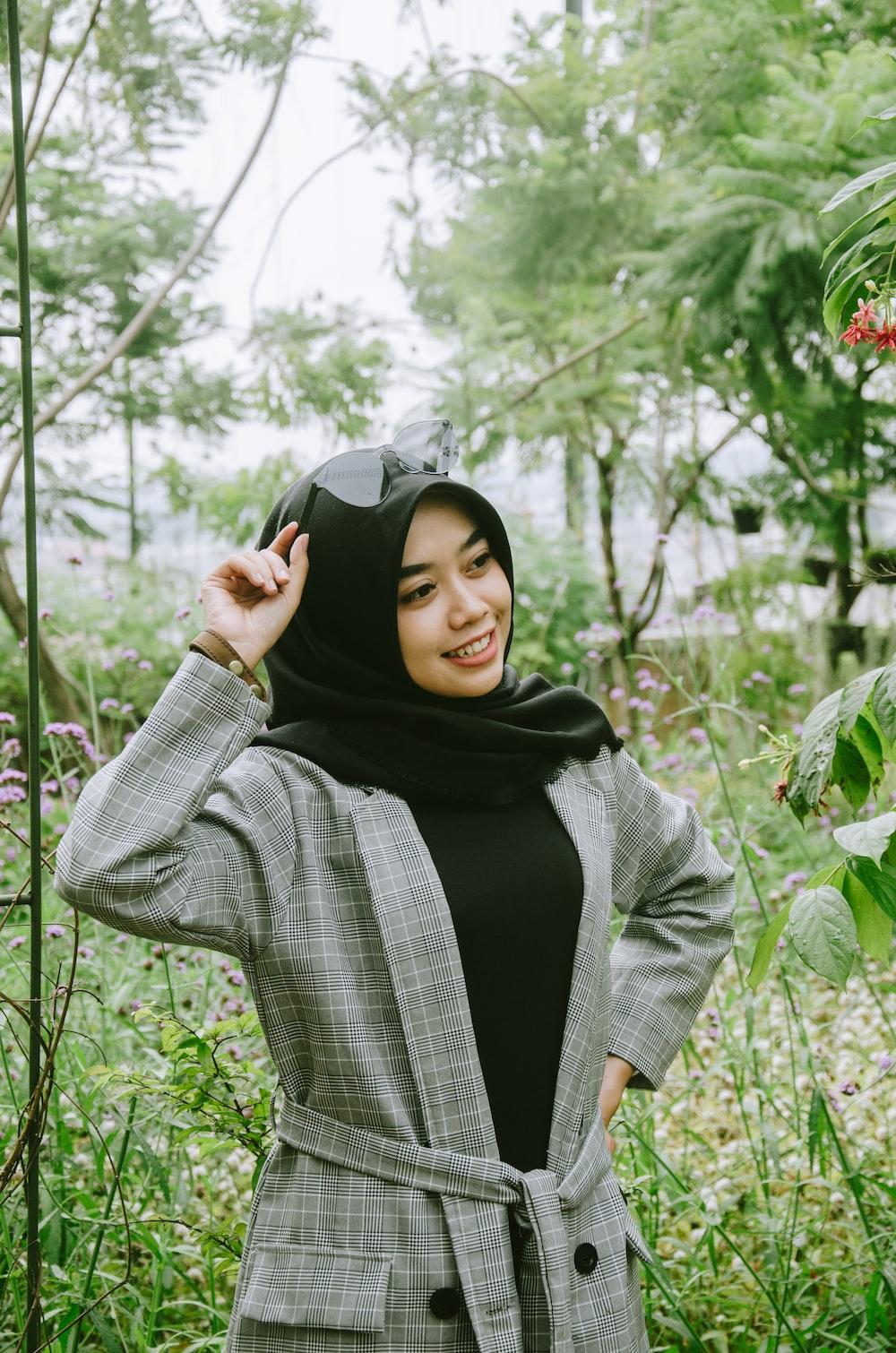 smiling woman wearing grey coat with black hijab