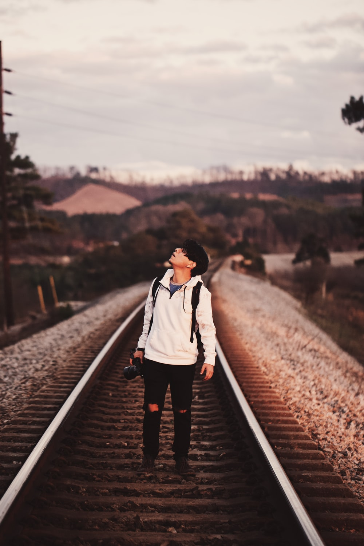 man standing on train rails