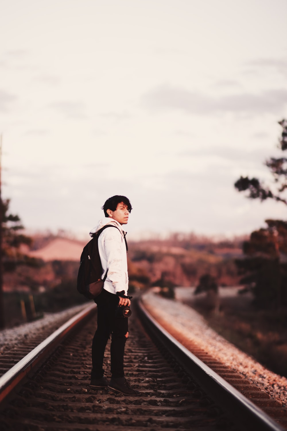 man standing on train rails during daytime