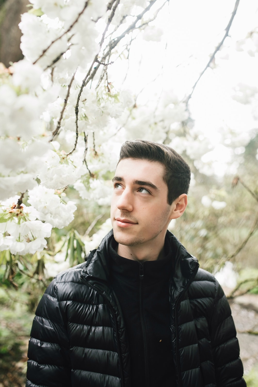 man in black bubble jacket standing under white flowering tree