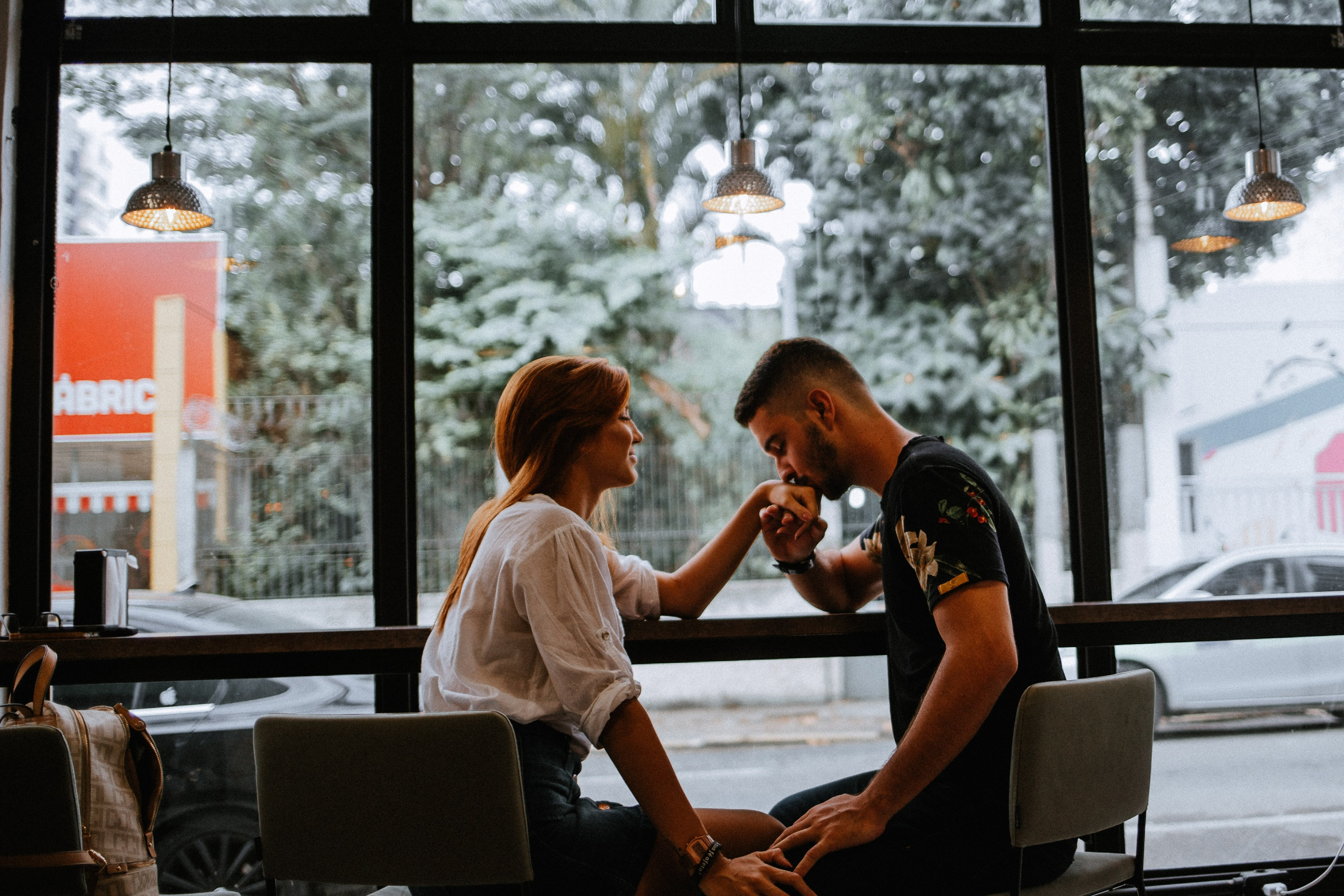 selective focus photography of man and woman sitting on dining set with man kissing hand of woman