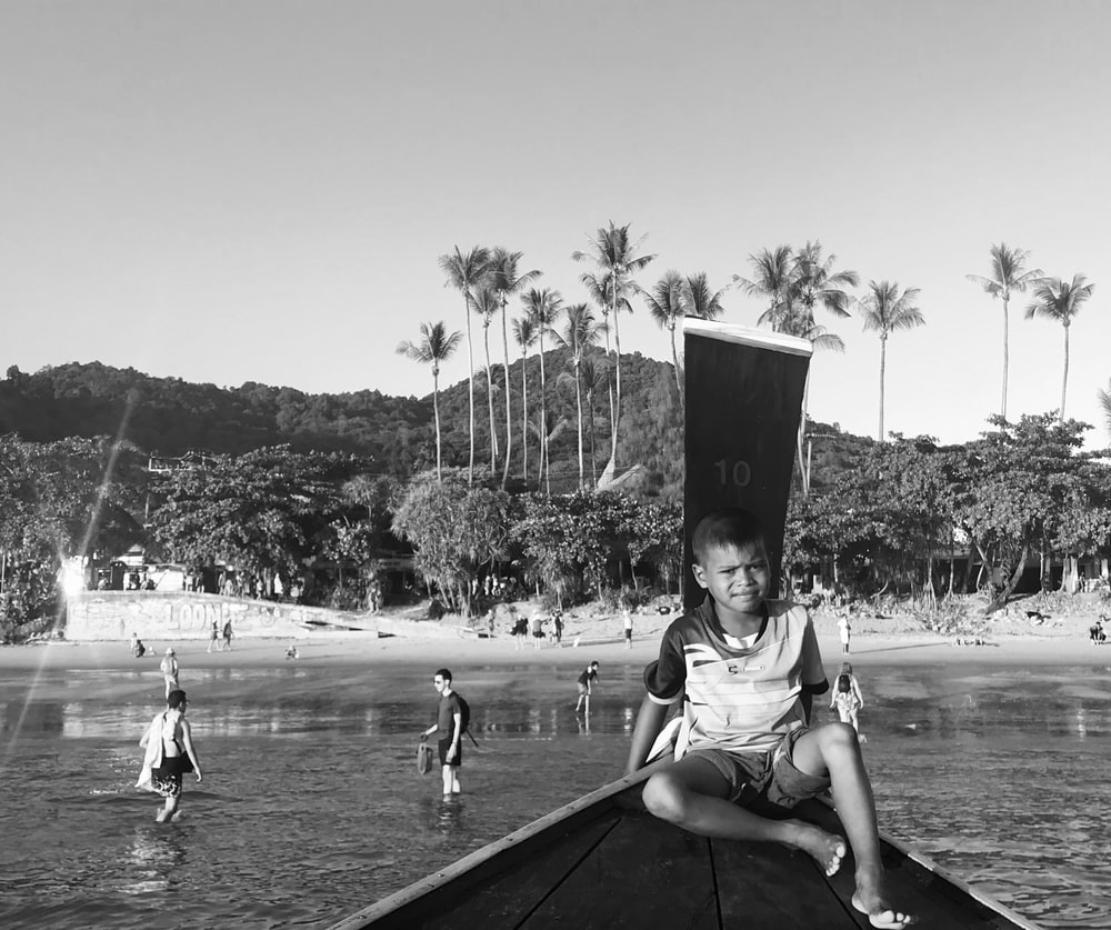grayscale photo of boy sitting on boat