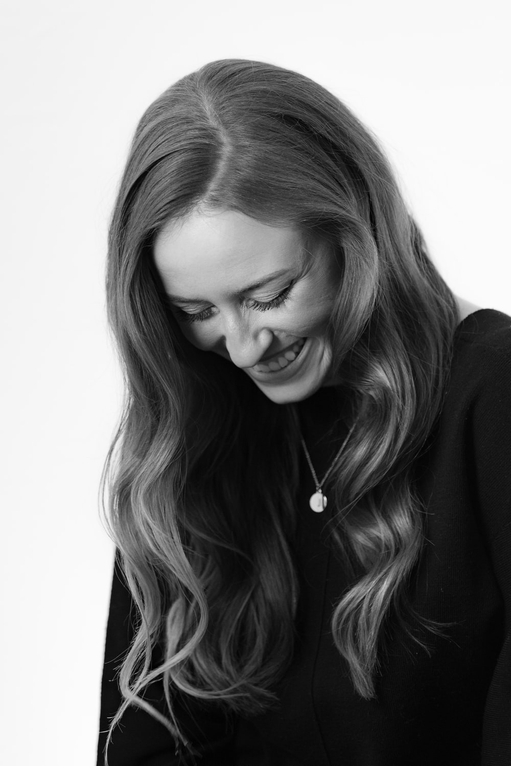 grayscale photography of smiling woman wearing black dress and pendant necklace